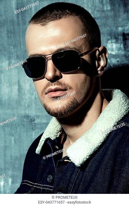 Sexual male model posing in jeans clothes and sunglasses. Short hair styling. Studio fashion shot