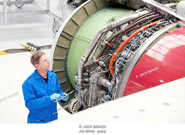 Engineer with digital tablet inspecting engine on passenger jet in hangar