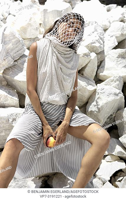 Fashion woman with head in web sitting on stones