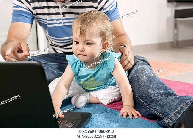 Baby concentrating playing computer laptop