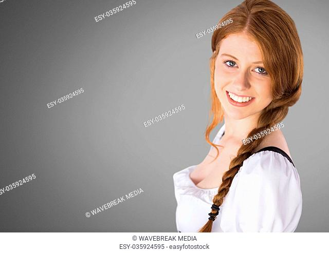 Beautiful young woman against grey background with braided hair
