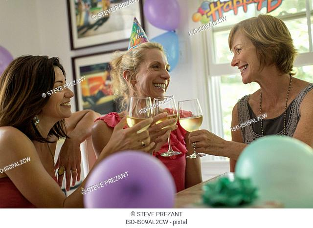 Three mature women toasting with wine glasses