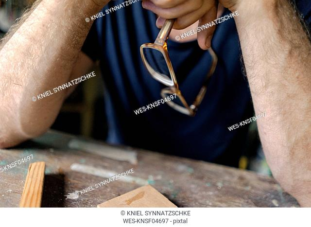 Close-up of man at workbench in workshop holding eyeglasses