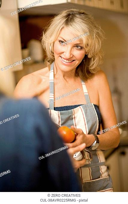 Woman slicing apple in kitchen