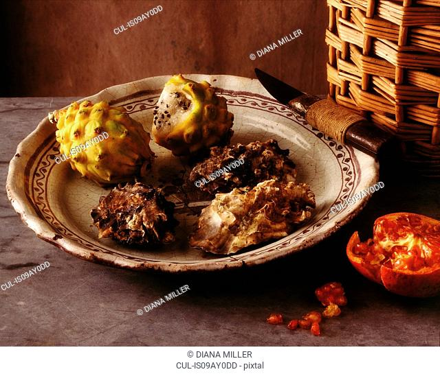 Still life of fresh oysters with exotic fruits on plate