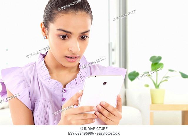 Shocked Teenage Girls looking at new tablet