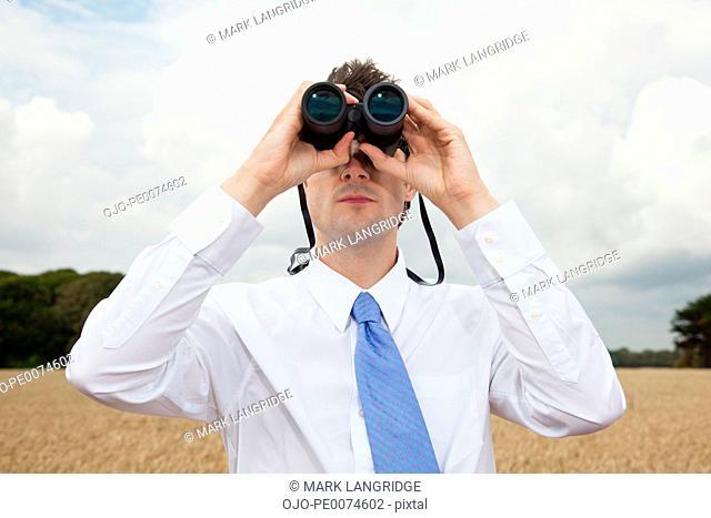 Businessman using binoculars outdoors