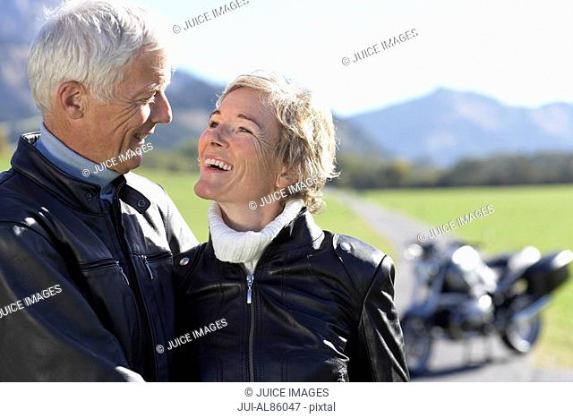 Senior biker couple smiling at each other with motorcycle in background in rural area