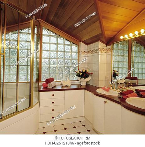 Hollywood-style light above vanity unit with double basins in modern bathroom with glass brick wall and wooden ceiling