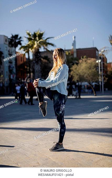 Spain, Barcelona, woman stretching leg on beach promenade
