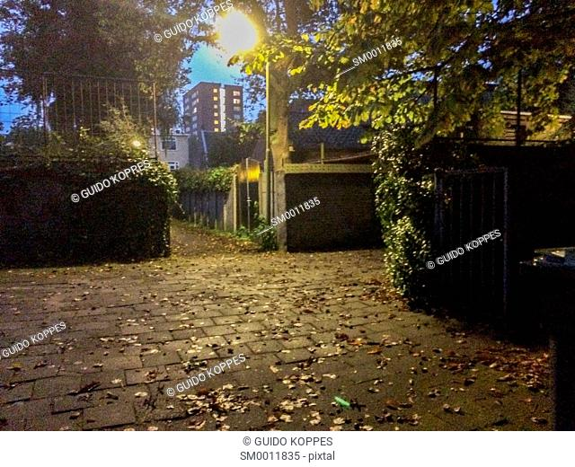 Tilburg, Netherlands. Courtyard and firebreak path during fall season at night