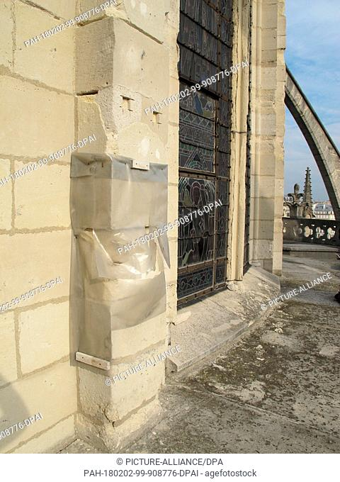 Damaged parts of the Notre-Dame Cathedral are covered with a plastic sheet for rain protection in Paris, France, 27 September 2017