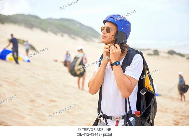 Male paraglider fastening helmet on beach