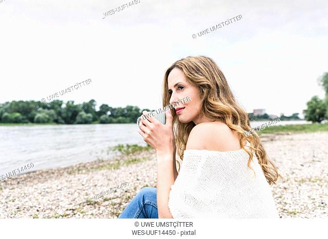 Woman sitting at the riverside drinking cup of coffee