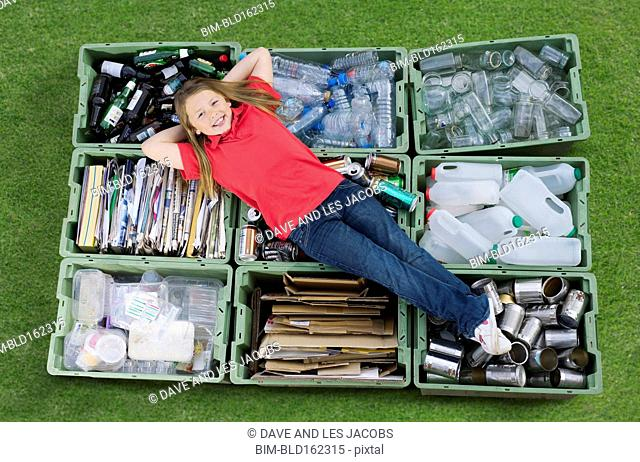 Caucasian teenage girl laying on recycling bins