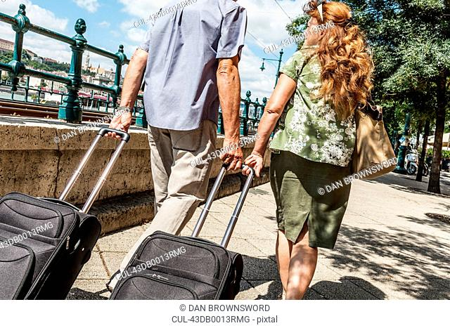 Older couple rolling luggage on street