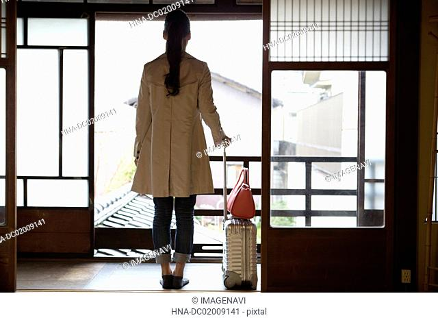 Young Japanese woman looking at outside from Japanese old house