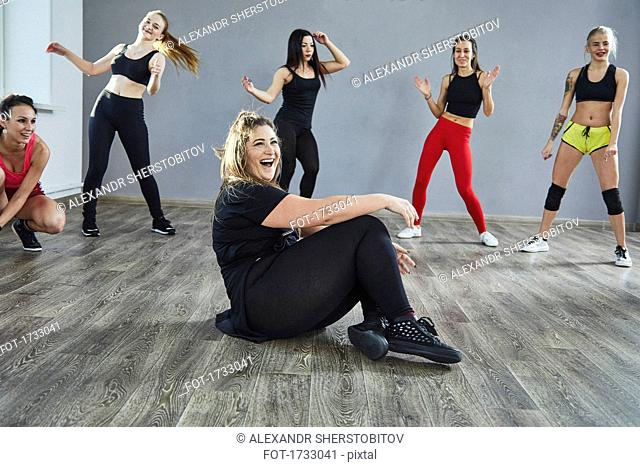 Laughing woman sitting on floor while dancing with friends at studio