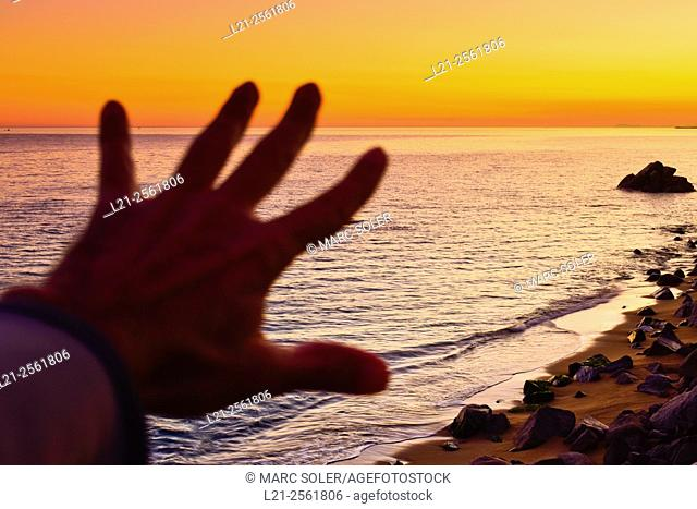 Blurred open hand. Sea, beach and rocks at sunset. Maresme, Barcelona province, Catalonia, Spain