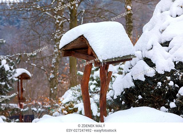 wooden bird feeder, birdhouse installed on winter garden in snowy day