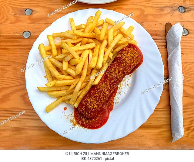 Original Berlin curry sausage, French fries, cutlery, napkin, wooden table, Berlin, Germany