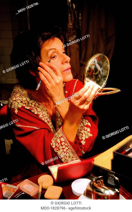 Italian actress Lella Costa painting her face accurately in front of a little mirror, before making the scene; the beloved performer puts on scene the monologue...