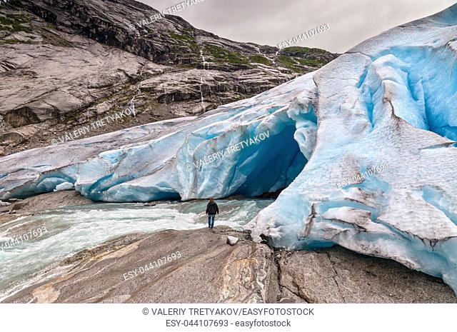 Jostedalsbreen glacier with the glacial river and man in Norway - melting because of Global warming
