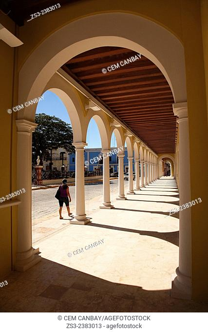 Woman walking along the building of the Nacional Library at Zocalo in the historical center listed as World Heritage Site by Unesco, Campeche City