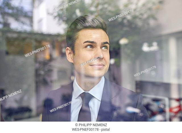 Portrait of young businessman behind glass pane in office looking up