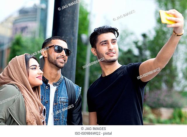 Three friends in street, taking selfie with smartphone