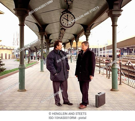 Two men talking on train platform