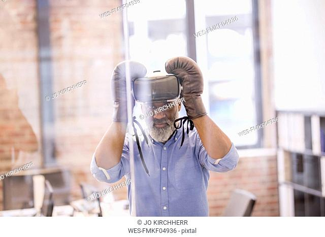 Portrait of businessman with Virtual Reality Glasses and boxing gloves in the office