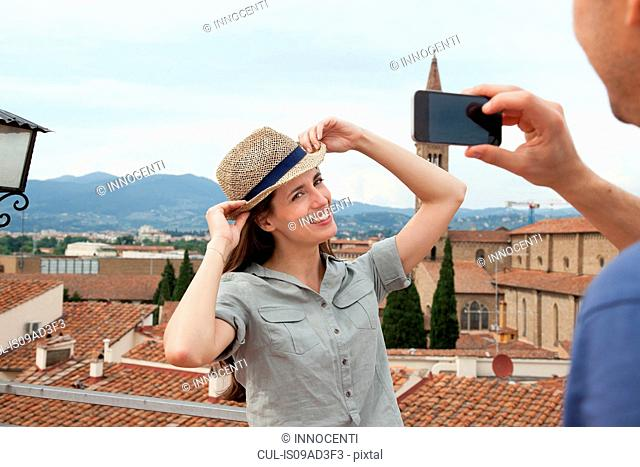 Man photographing woman with smartphone, Florence, Tuscany, Italy