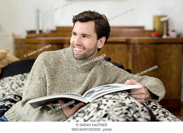 Portrait of smiling man sitting on the couch with a book