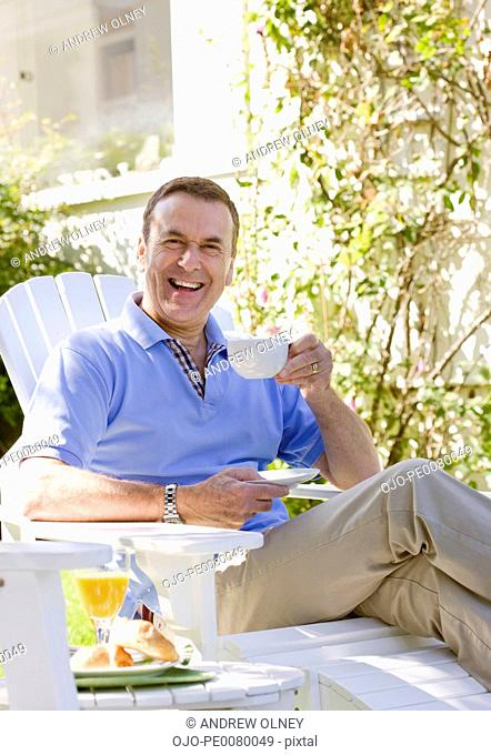 Man drinking coffee in backyard