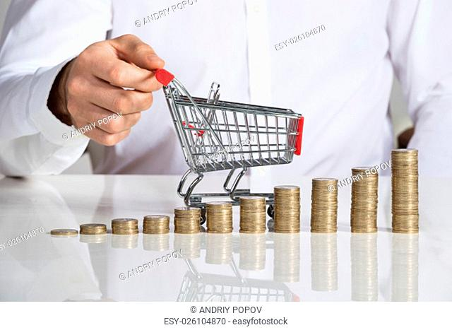 Midsection of businessman holding shopping cart by stacked coins arranged at office desk