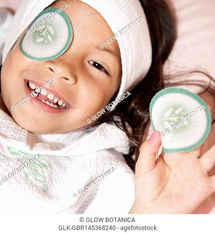 Portrait of a girl holding a cucumber slice shaped eye pad and smiling