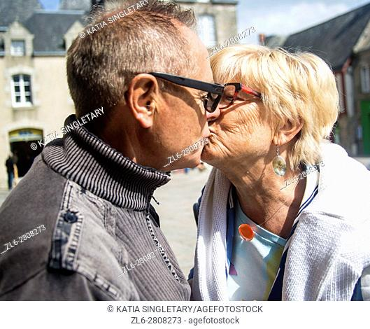 Older caucasian couple retired in love kissing each others, laughing and having a good times traveling together in summer. horizontal photo
