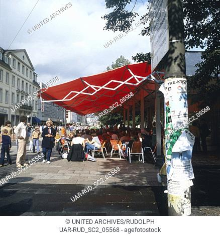 Voll bestztes Straßencafe in der Innenstadt von Kassel, Deutschland 1980er Jahre. Cafe with all places laid out at the city centre of Kassel, Germany 1980s