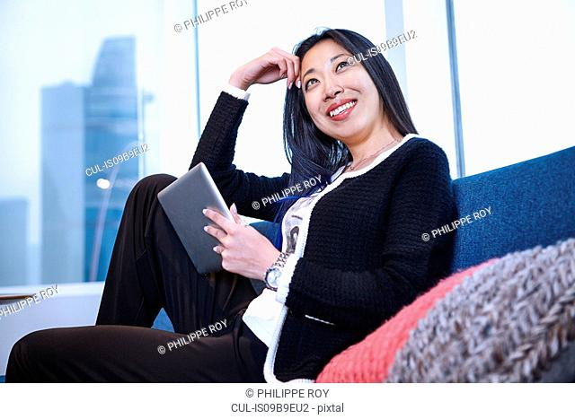 Woman on sofa using digital tablet smiling