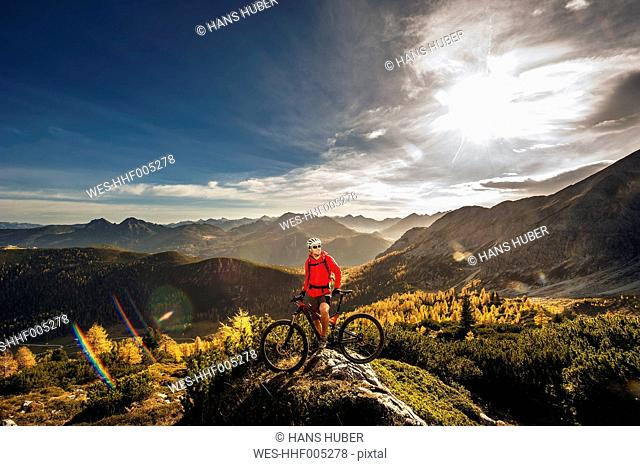 Austria, Altenmarkt-Zauchensee, young man with mountain bike at Low Tauern