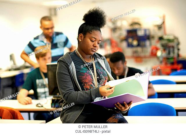 Female higher education student reading file in college classroom