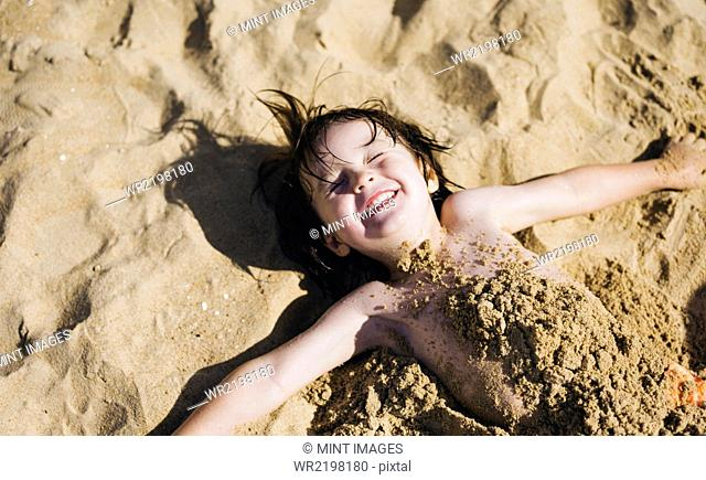 A boy lying on his back on the beach, his torso covered in sand, laughing