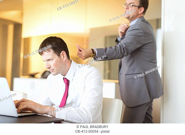 Angry businessman aiming rubber band at unsuspecting businessman working at laptop