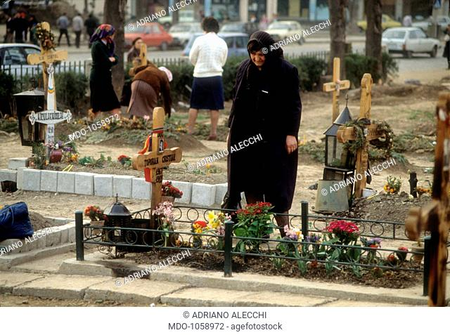 Elderly woman at the cemetery. An elderly woman looks at a grave in a cemetery built on a street. Romania, the Nineties