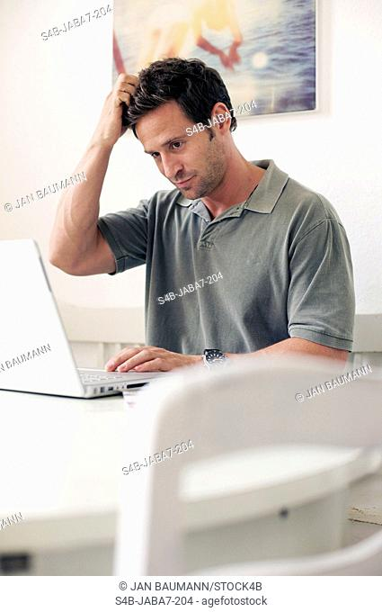 Man with laptop at home, Munich, Bavaria, Germany