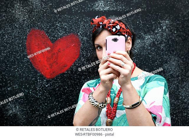 Woman taking a selfie next to heart painted on the wall