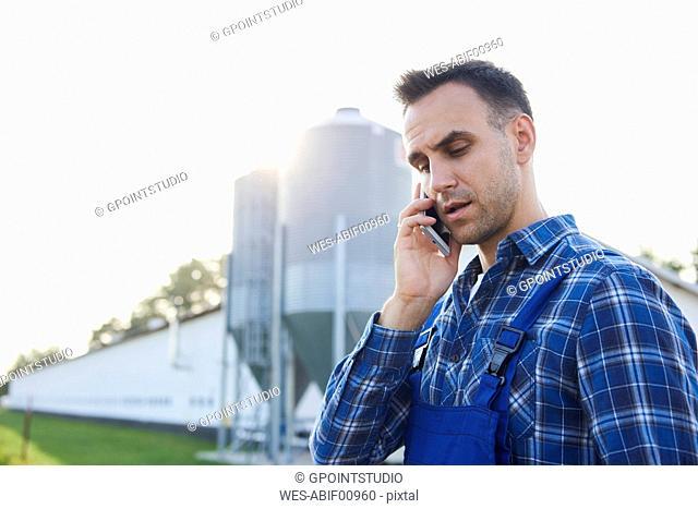 Farmer talking on cell phone on field