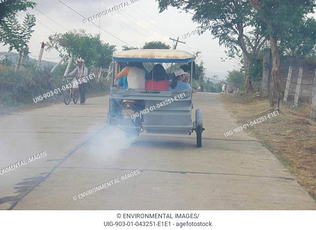 A smoke belching tricycle, climbs a steep hill, Palawan Island, Philippines