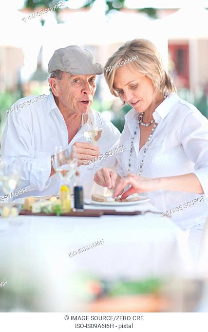 Older couple eating together outdoors